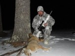 A dead coyote lays in front of an AR-15 George Sodergren used to kill the animal in Maine.